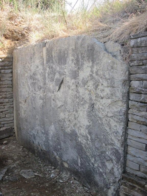 Fig. 2 – Grande lastra di Alberese della parete di fondo della tomba